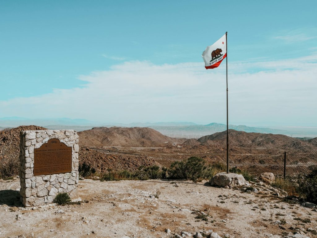 Picture shows the California Flag and the view across the desert from the Desert View Tower in Jacumba which is a stop on this Southwest Road Trip