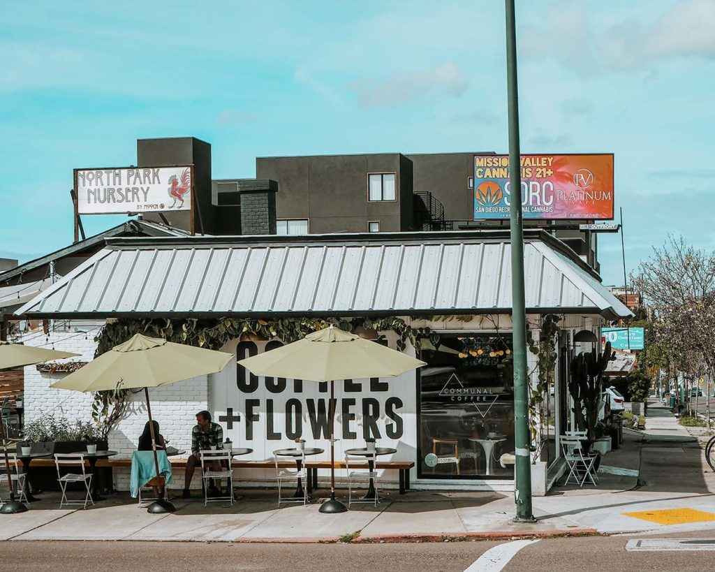 Communal Coffee San Diego pictured is the outside f the building with tables and mural that says Coffee and Flowers