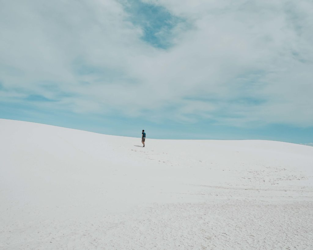White Sands National Monument. Pictured are Sand dunes and a man walking in the distance, leaving footsteps in the sand