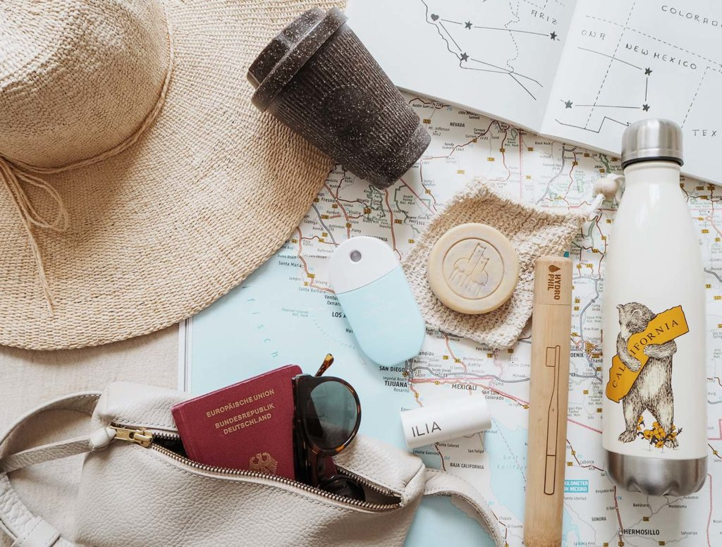 Eco-Friendly Travel Products spread out on a map displayed are a reuasable cup, water bottle, soap, a handbag with sunglasses and a passport a bamboo toothbrush and hand sanitizer